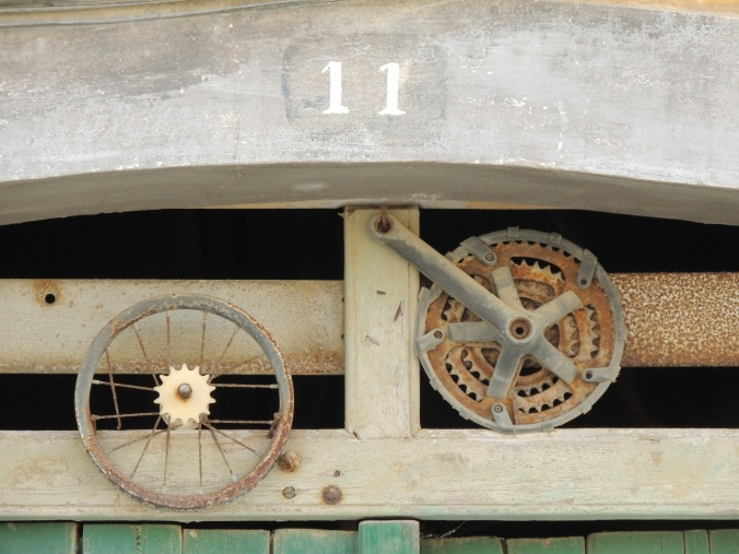 Close up above a door, with the number of 11 and two round shapes below. One looks like a bike wheel, the other a cog
