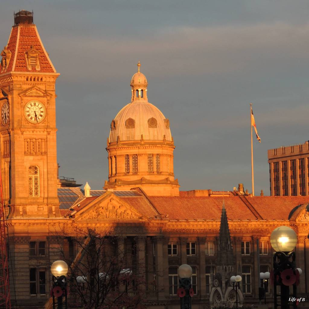 A clock tower, a domed building and a flag pole in the evening sunlight, with street lights just being turned on in the foreground